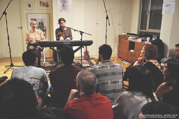 Músicos actuando en un salón con público