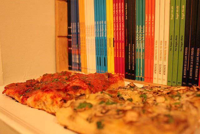Pizza diavola y pizza tutti funghi con guarnición de libros