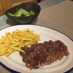 Carne a la brasa con patatas fritas y ensalada