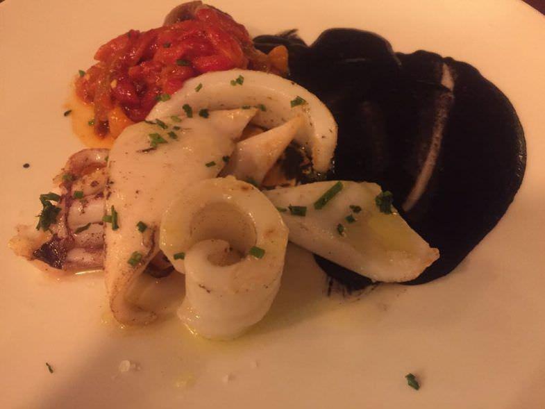 Calamar braseado con salsa de su tinta, asadillo de pimientos y cebollitas