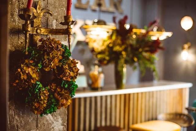 Corona floral en verde y dorado.