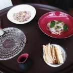Preparación en mesa de los platos de la lasaña de marisco y el tartar con sus respectivas salsas