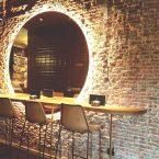 Se mantiene la pared de ladrillo existente y se decora con espejos retoriluminados