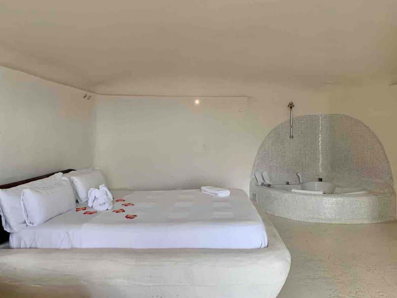 Interior de la cueva con cama extragrande y jacuzzi en Hotel Spa Las Nubes